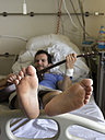 Young man playing guitar in hospital bed - LA000132