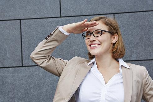 Germany,  Businesswoman shielding eyes - RKNF000151