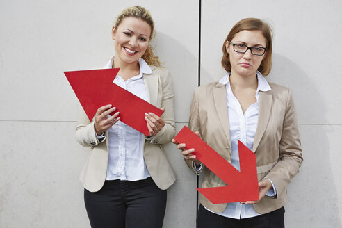 Germany, Businesswomen holding arrows pointing in opposing directions - RKNF000136