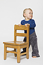 Baby boy with sad face holding onto chair, studio shot - MUF001376
