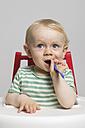 Baby boy holding spoon, studio shot - MUF001399