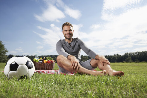 Germany, Cologne, man sitting on blanket with picnic basket an d soccer ball - PDF000392