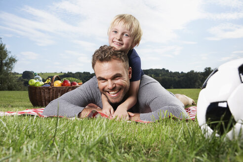 Germany, Cologne, Father and son playing around on picnic blanket - PDF000395
