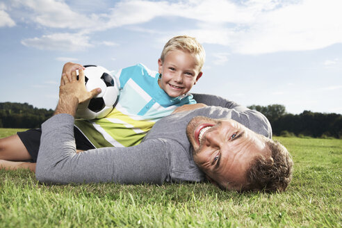Germany, Cologne, Father and son playing soccer - PDF000407