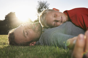Germany, Cologne, Father and son sleeping in meadow - PDF000425
