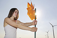 Germany, North Rhine Westphalia, Neuss, female teenager at wind farm holding windmill - JATF000327