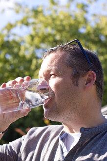 Germany, Schleswig-Holstein, Kiel, man drinking a glass of water - JFE000214