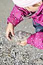 Denmark, Ringkoebing, little girl on beach holding jellyfish - JFEF000200