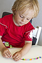 Germany, Schleswig-Holstein, Kiel, little girl threading pearls - JFE000228