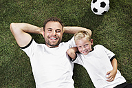 Germany, Father and sun lying on lawn, wearing football shirts - PDF000438