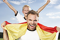 Germany, Cologne, Father and son cheering in football outfit - PDF000444