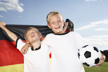 Germany, Cologne, Two boys wearing football shirts, holding German flag - PDF000453