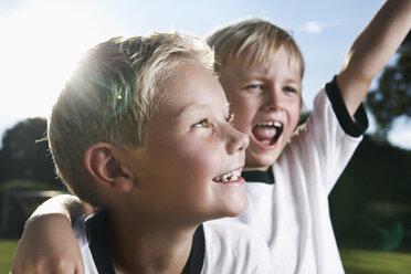 Germany, Cologne, Two boys playing football, wearing football shirts - PDF000456