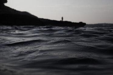 Croatia, Mediterranean Sea, ocean, person standing at rock - FMKF000914
