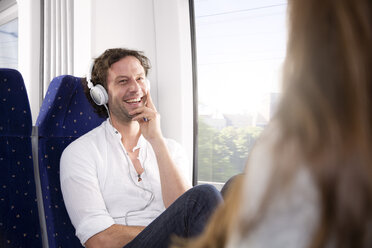 Man with headphones in a train smiling at woman - KFF000257