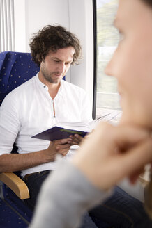 Man reading book in a train - KFF000281