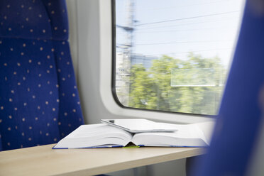 Book and digital tablet in a train - KFF000251