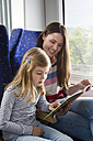 Mother and daughter reading book in a train - KFF000245