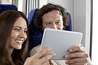 Couple using digital tablet in a train - KFF000234