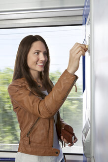 Woman at ticket machine in a train - KFF000275