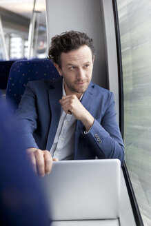 Businessman with laptop in a train - KFF000222