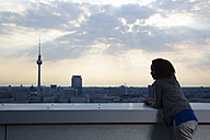 Germany, Berlin, Young woman on rooftop terrace, looking at view - FKF000274