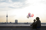 Germany, Berlin, Young women on rooftop terrace, holding balloons - FKF000281