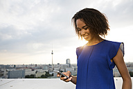 Germany, Berlin, Young woman using mobile phone - FKF000268