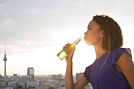 Germany, Berlin, Young woman drinking beer - FKF000267