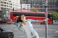 Germany, Berlin, Young women in the city, holding onto pole - FKF000294