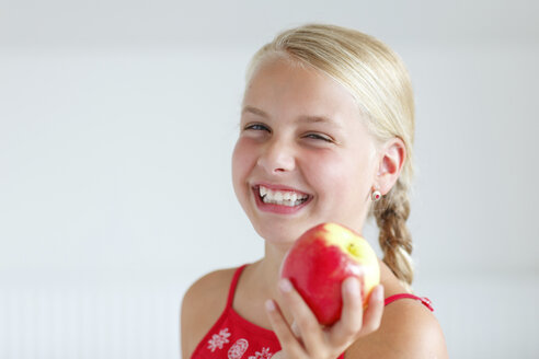Smiling blond girl holding an apple - HR000011