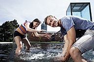 Germany, Bavaria, Munich, Couple splashing with water at fountain - RBF001351