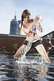 Germany, Bavaria, Munich, Young woman splashing with water at fountain - RBF001354