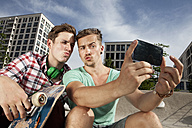 Germany, Bavaria, Munich, Two friends with smartphone taking self-portrait - RBF001362