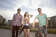Germany, Bavaria, Munich, Friends walking with skateboard and BMX bicycle - RBF001365