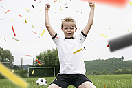 Boy in soccer jersey cheering on soccer pitch - PDF000462