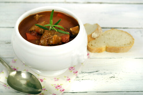 Goulash soup with bread on wooden table - ODF000566