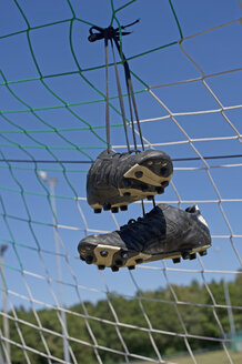 Germany, Bavaria, Munich, football shoes hanging in football net - ASF005200