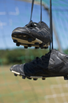 Germany, Bavaria, Munich, football shoes hanging in football net - ASF005203