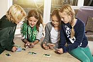 Four children playing card game in living room - GDF000221