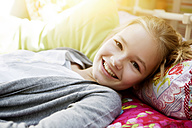 Smiling girl lying on bed, portrait - GDF000223