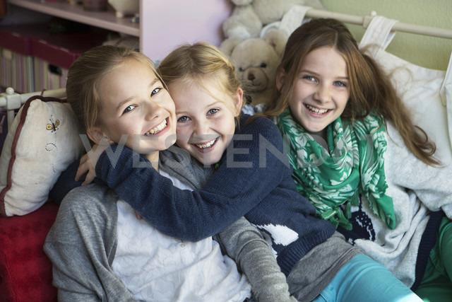Three happy girls on bed - GDF000225