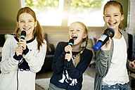 Three girls singing with microphone - GDF000226