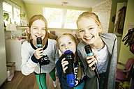 Three girls singing with microphone - GDF000228