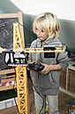 Blond boy playing with toy crane - GDF000233