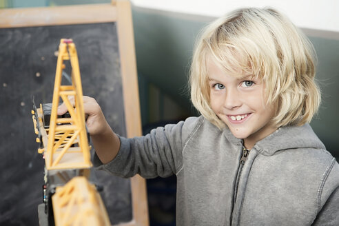 Blond boy playing with toy crane - GDF000234