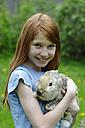 Girl holding a dwarf rabbit - LB000352