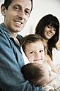 Young family with male newborn and little daughter sitting on sofa at home - JATF000385