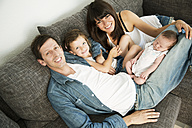 Young parents with male newborn and little daughter sitting on sofa at home - JATF000430