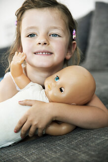 Portrait of smiling little girl lying on sofa with her doll, close-up - JATF000390